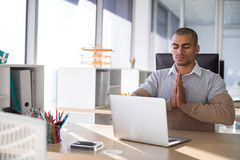 Male executive doing yoga. In office Royalty Free Stock Images