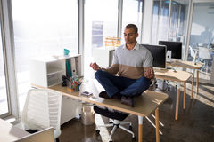 Male executive doing yoga in office Stock Images