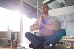 Male executive doing yoga in office Stock Image