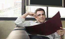 Male Executive With Folder Sitting On Sofa Royalty Free Stock Photo