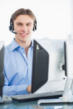 Male executive with headset using computer at desk Stock Images