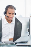 Male executive with headset using computer at desk. Portrait of a smiling male executive with headset using computer at office desk Royalty Free Stock Photography