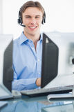 Male executive with headset using computer at desk. Portrait of a smiling male executive with headset using computer at office desk Royalty Free Stock Photo