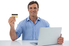 Male executive holding debit card against white background Stock Photos
