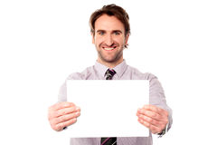 Male executive holding out blank ad board Royalty Free Stock Photography