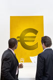 Male executive looking at Euro sign over white background Royalty Free Stock Image