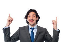 Male executive looking and pointing upwards Royalty Free Stock Images