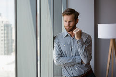 Male executive looking through window in office Stock Image