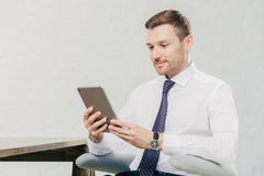 Male executive manager in white shirt and tie, holds tablet computer, searches necessary information in internet, connected to wif. I in office. People, business Royalty Free Stock Photos