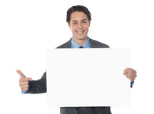 Male executive pointing towards blank billboard Royalty Free Stock Photo