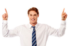Male executive pointing upwards. Young businessman pointing upwards over white Stock Photo