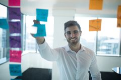 Male executive reading sticky note. In office royalty free stock images