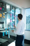 Male executive reading sticky note Stock Photo
