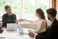Male executive shaking hands with female coworker, teamwork intr. Young male executive in formal suit shaking hands with attractive female coworker. Employees Stock Photography