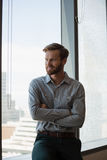 Male executive sitting with arms crossed in office Royalty Free Stock Image