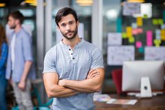 Male executive standing with arms crossed in office Stock Image