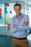 Male executive standing with arms crossed in office Stock Images