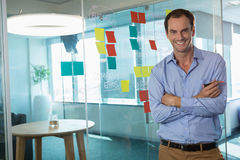 Male executive standing with arms crossed in office Stock Photos