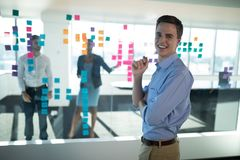 Male executive standing in office with colleagues in background stock photos