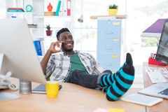 Male executive talking on mobile phone while relaxing at his desk in office Royalty Free Stock Images
