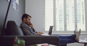 Male executive talking on mobile phone while using laptop in a modern office 4k. Side view of Caucasian male executive talking on mobile phone while using laptop stock footage