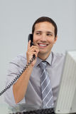 Male executive talking on phone. At his desk Royalty Free Stock Photography