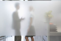Male Executive Talking To Female Colleague Behind Translucent Wa Royalty Free Stock Images