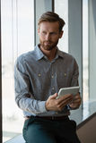 Male executive using digital tablet near window Stock Images