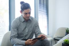Male executive using digital tablet in waiting area. Of office Royalty Free Stock Photography