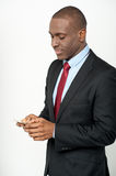 Male executive using his mobile phone. Smiling businessman sending message using mobile phone Royalty Free Stock Image
