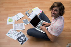 Male executive using laptop while sitting on floor in the office Stock Photo