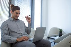 Male executive using laptop in waiting area. Of office Royalty Free Stock Image