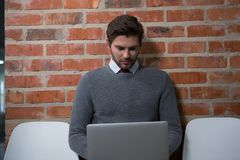 Male executive using laptop in waiting area. Of office Stock Images