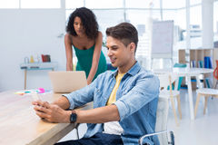 Male executive using mobile phone while female executive working on computer. In the office Royalty Free Stock Photos