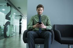 Male executive using mobile phone in waiting area royalty free stock photography