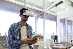 Male executive using virtual reality headset and digital tablet Royalty Free Stock Images
