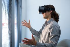 Male executive using virtual reality headset in waiting area. Of office Stock Photography