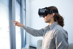 Male executive using virtual reality headset in waiting area. Of office Stock Images