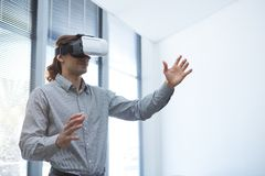 Male executive using virtual reality headset in waiting area. Of office Stock Photos