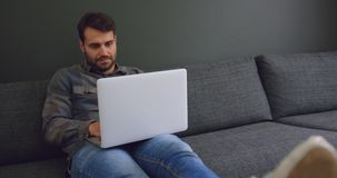 Male executive working on laptop in a modern office 4k. Front view of Caucasian male executive working on laptop in a modern office. He is sitting on the sofa 4k stock footage