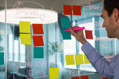 Male executive writing on glass board with a marker. In office Stock Photos