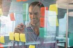 Male executive writing on glass board with a marker. In office Stock Image