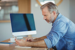 Male executive writing in organizer while using mobile phone. In office Stock Image