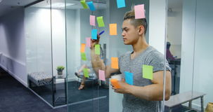 Male executive writing on stick notes stock video