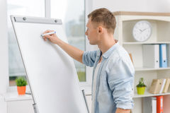 Male executive is writing on whiteboard Royalty Free Stock Photography