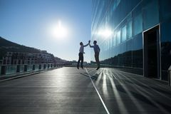 Male executives giving high five to each other. In Male executives walking together in office premises Stock Photography