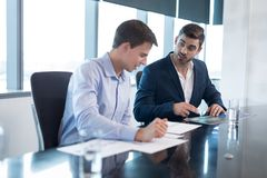 Male executives having discussion over graph. In boardroom royalty free stock images