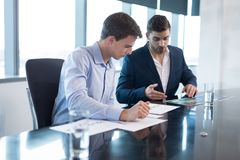 Male executives having discussion over graph. In boardroom stock photography