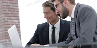 Male executives in office, looking at computer. Concept of teamwork stock photography