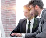 Male executives in office, looking at computer. Concept of teamwork stock images